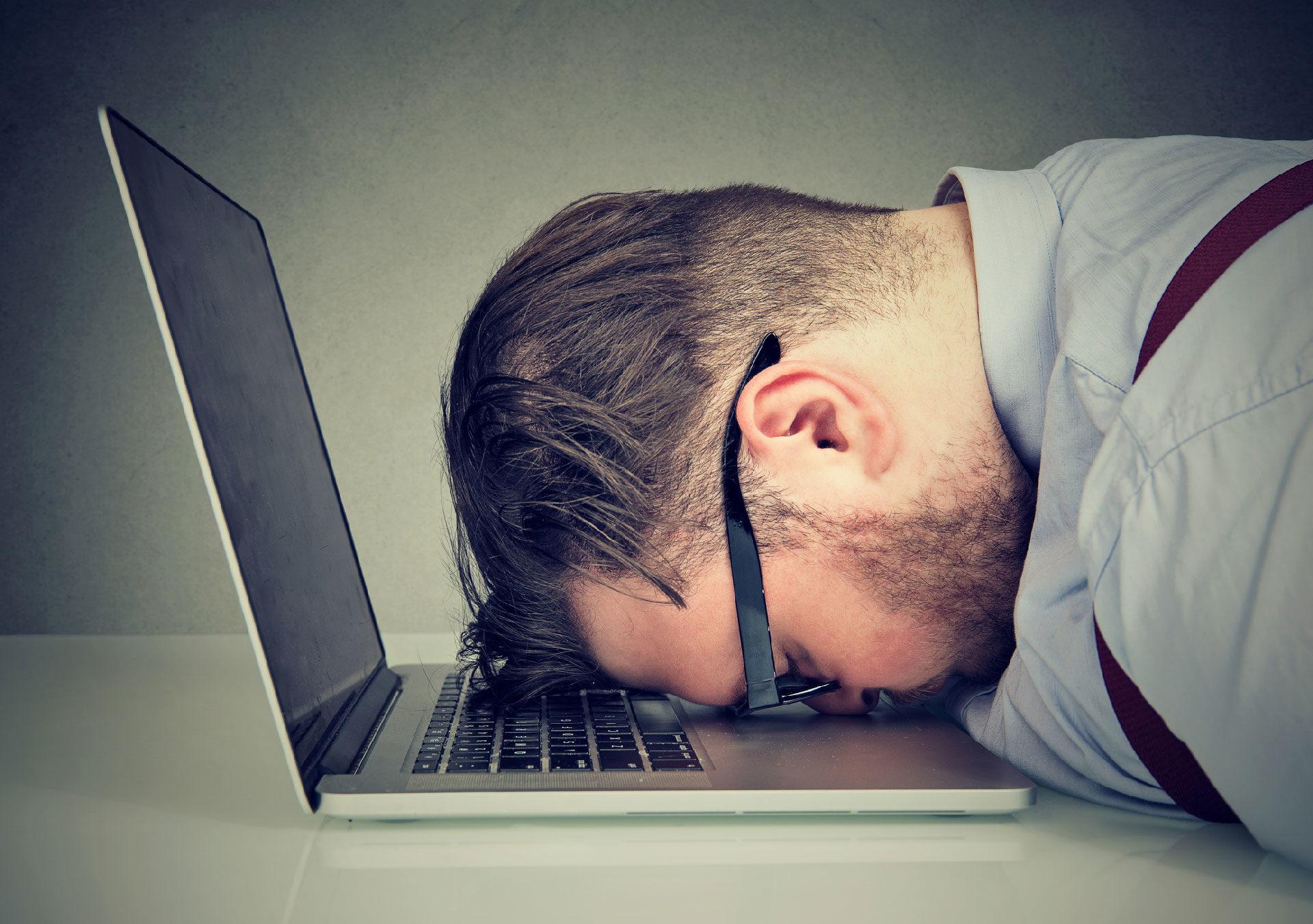 Digitale stresset - Oppgitt mann med pannen i en datamaskin